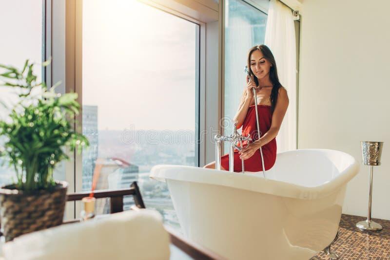 Λεπτή νέα γυναίκα στη συνεδρίαση πετσετών στην μπανιέρα στο πολυτελές λουτρό στοκ εικόνα