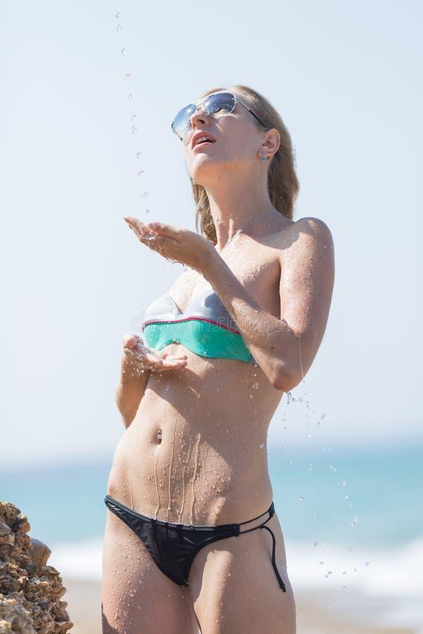 Λεπτή νέα γυναίκα στο μπικίνι κάτω από το ρέοντας νερό στοκ εικόνα