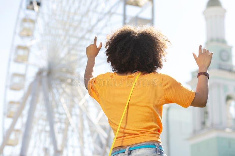 Λεπτή σγουρή γυναίκα που προσποιείται να αγγίξει τα κτήρια στοκ φωτογραφία με δικαίωμα ελεύθερης χρήσης