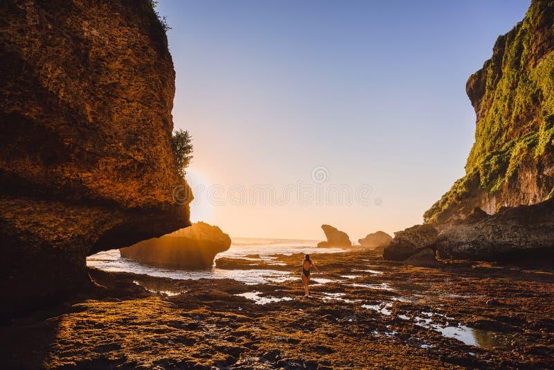 Λεπτή τοποθέτηση γυναικών κοντά στον ωκεανό με τους βράχους και τα χρώματα ηλιοβασιλέματος Ταξιδιώτης γυναικών στον ωκεανό στοκ φωτογραφίες