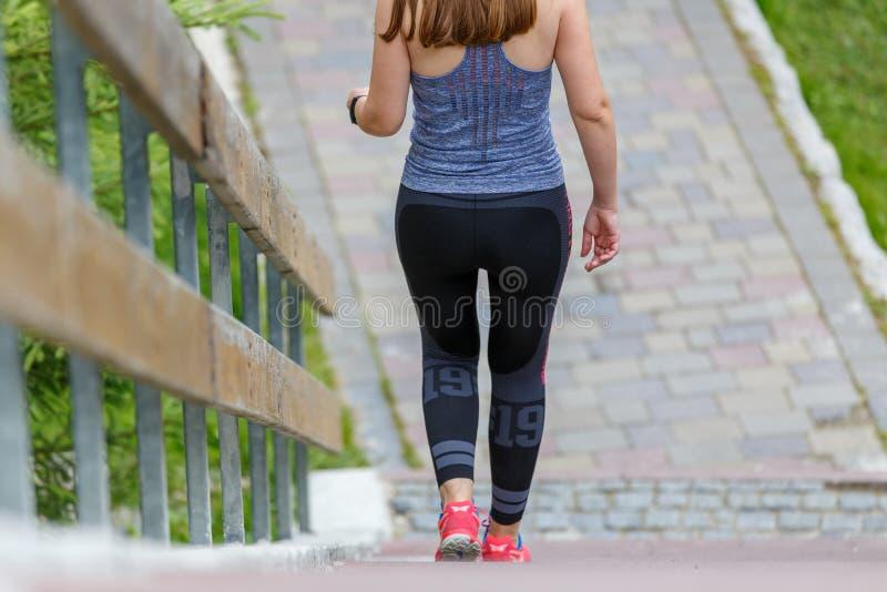 Λεπτή φίλαθλη γυναίκα που κατεβαίνει τα σκαλοπάτια υπαίθρια στοκ εικόνες
