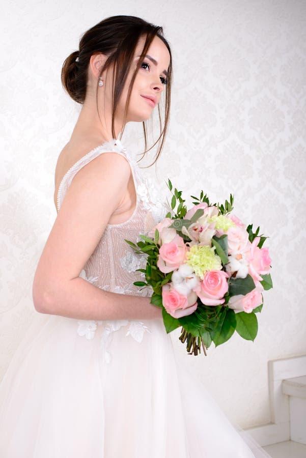 Λεπτή όμορφη γυναίκα που φορά το πολυτελές γαμήλιο φόρεμα πέρα από το άσπρο υπόβαθρο στούντιο Πανέμορφα λουλούδια εκμετάλλευσης ν στοκ φωτογραφίες