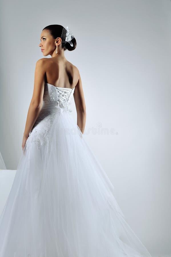 Λεπτή όμορφη γυναίκα που φορά το πολυτελές γαμήλιο φόρεμα στοκ εικόνα με δικαίωμα ελεύθερης χρήσης