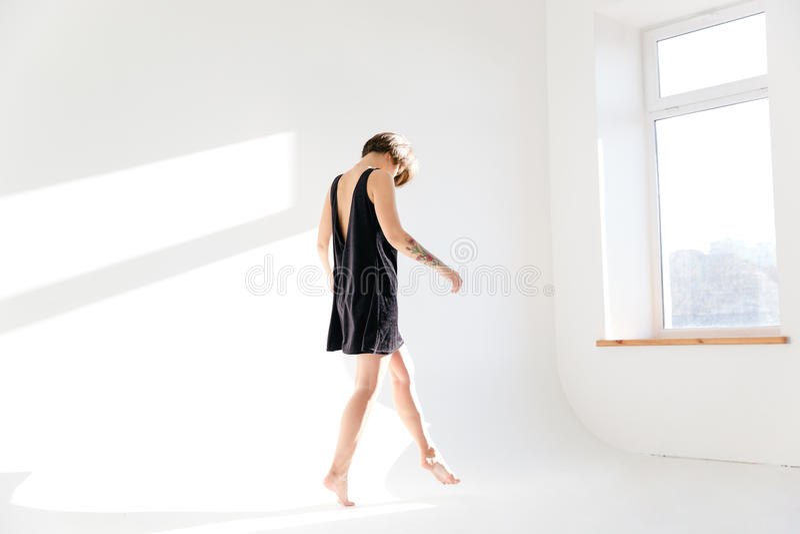 Λεπτή όμορφη νέα γυναίκα στο μαύρο φόρεμα που περπατά tiptoe στοκ εικόνες με δικαίωμα ελεύθερης χρήσης