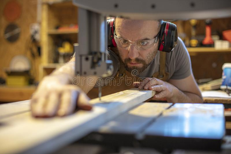 Λεπτομέρεια ενός ξυλουργού προσηλωμένου στην κοπή ενός κομματιού του ξύλου με την ακρίβεια στοκ φωτογραφία με δικαίωμα ελεύθερης χρήσης