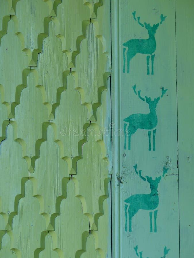 Λεπτομέρεια ενός χαραγμένου πράσινου ξύλινου τοίχου με τους διαφορετικούς τύπους συστάσεων με μερικά σκίτσα των ταράνδων στη Ρουμ στοκ εικόνα με δικαίωμα ελεύθερης χρήσης