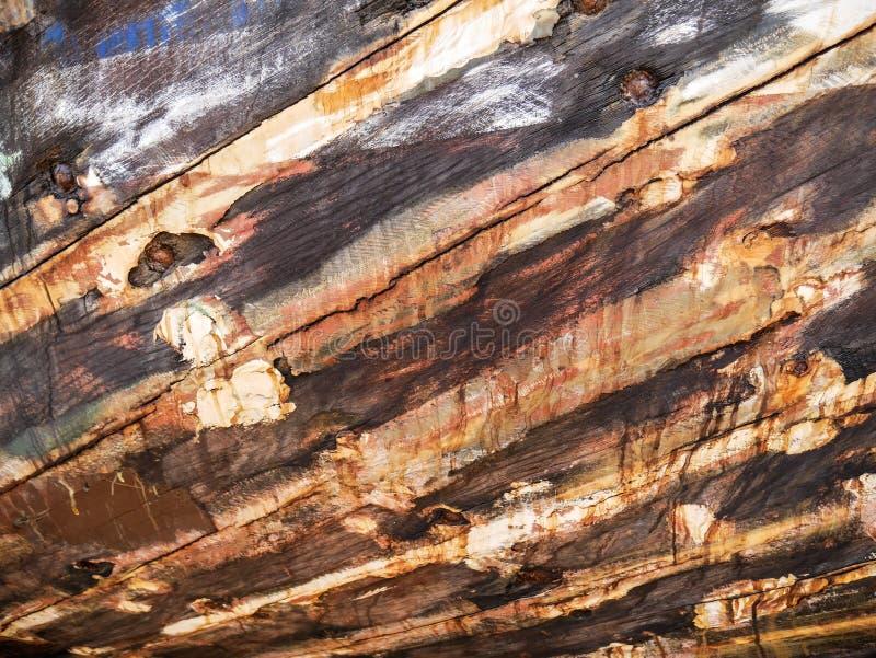 Λεπτομέρεια και κινηματογράφηση σε πρώτο πλάνο της παλαιάς και χρωματισμένης ξύλινης φλούδας βαρκών, παλαιά ζωγραφική με τις ρωγμ στοκ εικόνα