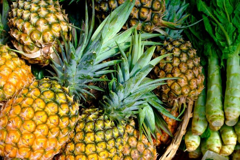 Λεπτομέρεια κινηματογραφήσεων σε πρώτο πλάνο του ανανά και των ασιατικών vegetalbles στην αγορά στοκ φωτογραφία