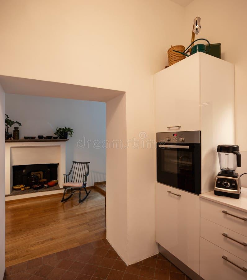 Λεπτομέρεια κουζινών με τη ανοιχτή πόρτα, τη λικνίζοντας καρέκλα και την εστία στοκ φωτογραφία με δικαίωμα ελεύθερης χρήσης