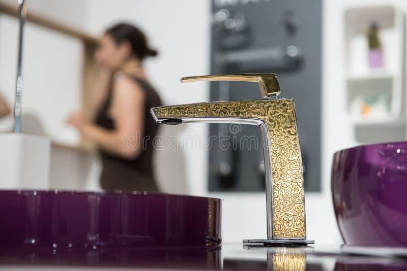 Λεπτομέρεια λουτρών στο νέο σπίτι πολυτέλειας: νεροχύτης και χρυσή στρόφιγγα με τη μερική άποψη της γυναίκας κοντά στον καθρέφτη στοκ φωτογραφίες με δικαίωμα ελεύθερης χρήσης