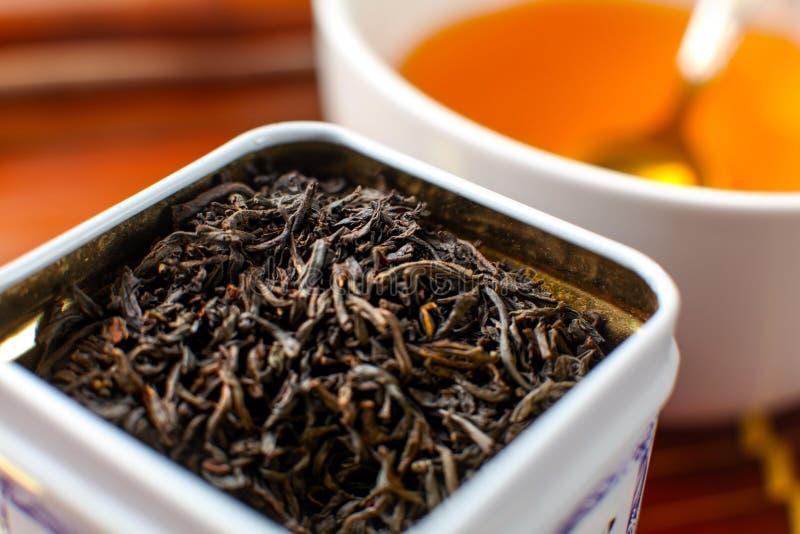 Λεπτομέρεια στην άσπρη δόση μετάλλων με το τσάι χαλαρών φύλλων, και θολωμένο φλυτζάνι στοκ εικόνα με δικαίωμα ελεύθερης χρήσης