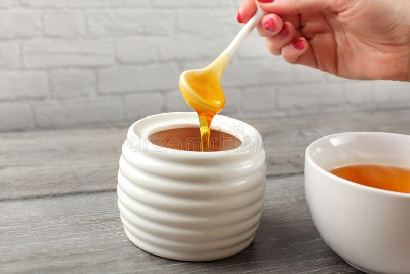 Λεπτομέρεια στη γυναίκα το μικρό κεραμικό κουτάλι, που γεμίζουν που κρατά με το μέλι, στοκ εικόνες
