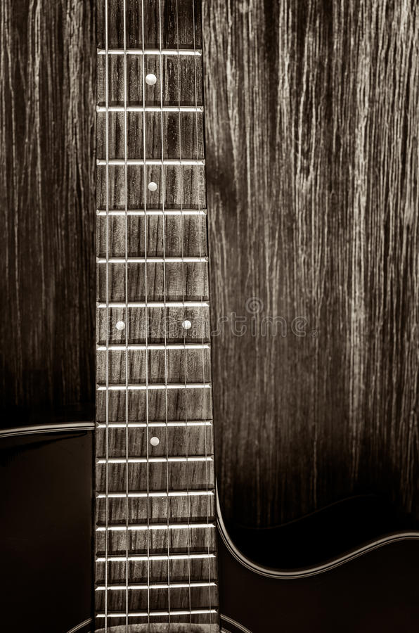 Λεπτομέρεια της ακουστικής κιθάρας στο εκλεκτής ποιότητας ύφος στο ξύλινο υπόβαθρο στοκ εικόνες