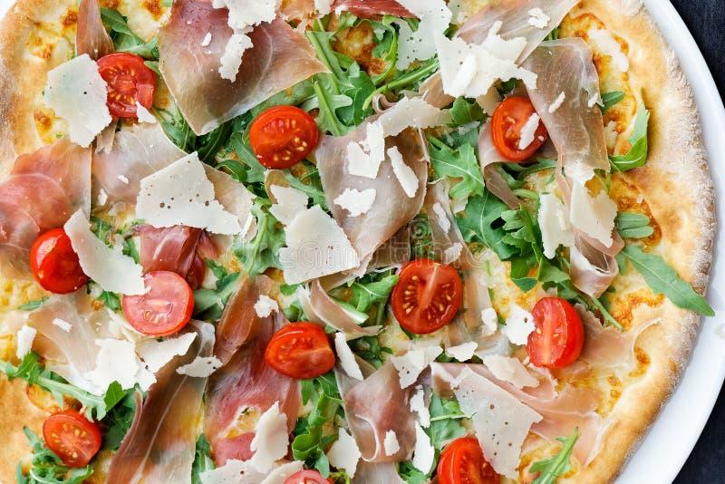 Λεπτομέρεια της πίτσας prosciutto με τις ντομάτες κερασιών και του rucola από στοκ φωτογραφία με δικαίωμα ελεύθερης χρήσης
