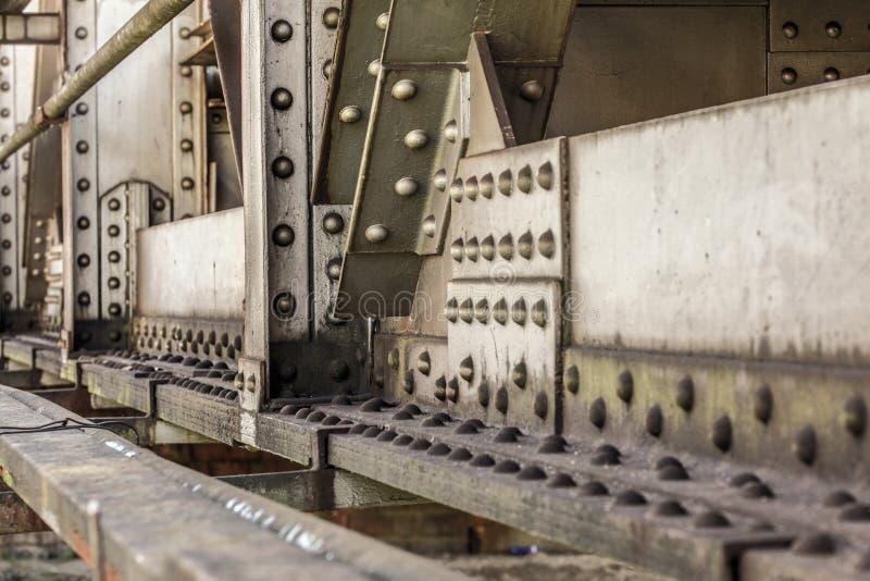 Λεπτομέρεια της παλαιάς γέφυρας ραγών, των μεγάλων καρυδιών, των μπουλονιών και των καρφιών ορατών αφηρημένη ανασκόπηση βιομη&ch στοκ φωτογραφία με δικαίωμα ελεύθερης χρήσης