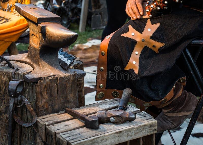 Λεπτομέρεια του ιματισμού και των εργαλείων του μεσαιωνικού σιδηρουργού στον παραδοσιακό ετήσιο μεσαιωνικό εορτασμό αγοράς στο Πο στοκ εικόνα