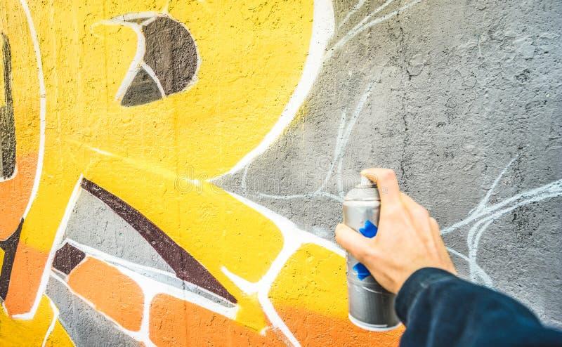 Λεπτομέρεια του καλλιτέχνη οδών που χρωματίζει τα ζωηρόχρωμα γκράφιτι στο δημόσιο τοίχο στοκ εικόνες