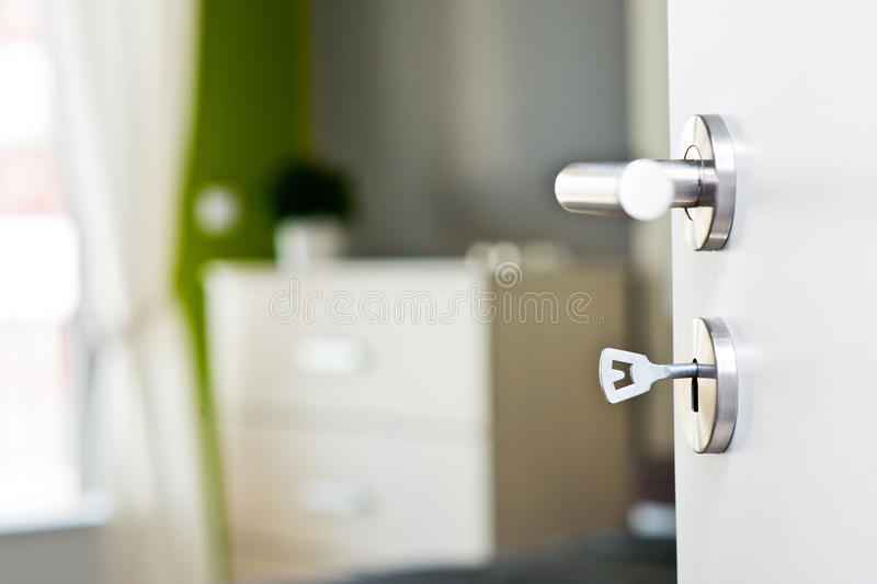 Λεπτομέρεια του κλειδιού στην πόρτα με την όμορφη σύγχρονη κρεβατοκάμαρα στοκ εικόνες
