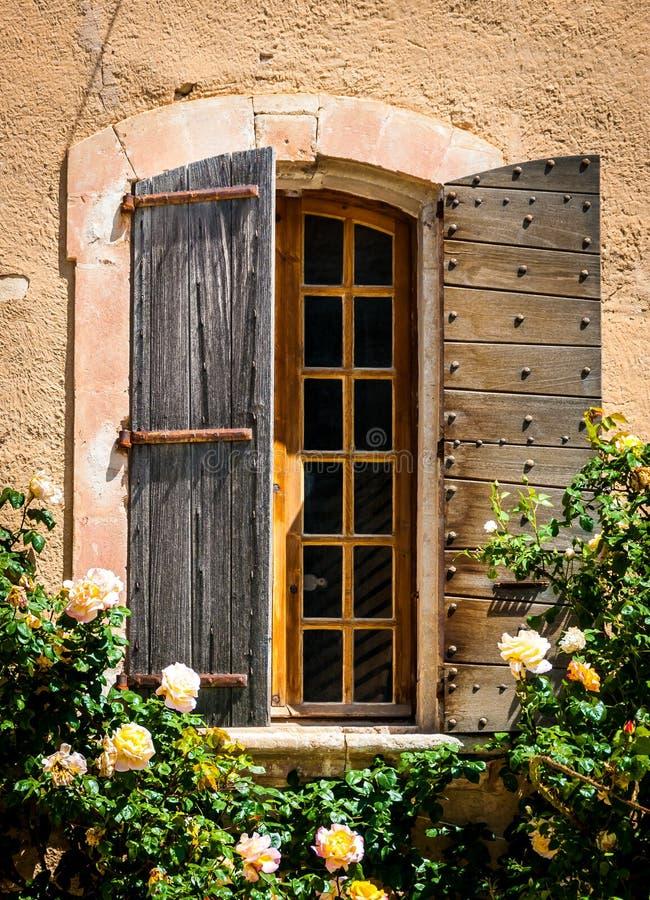 Λεπτομέρεια του παλαιού εκλεκτής ποιότητας ξύλινου παραθύρου με τα άγρια τριαντάφυλλα στοκ εικόνες με δικαίωμα ελεύθερης χρήσης
