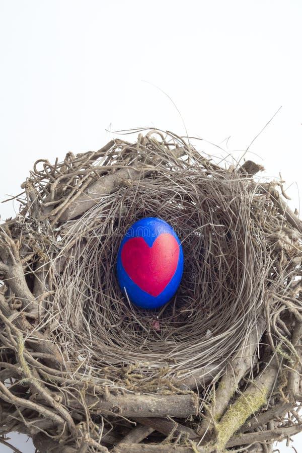 Λεπτομέρεια του χρωματισμένου αυγού Πάσχας με μια κόκκινη καρδιά που τοποθετείται σε μια φωλιά ι στοκ εικόνες