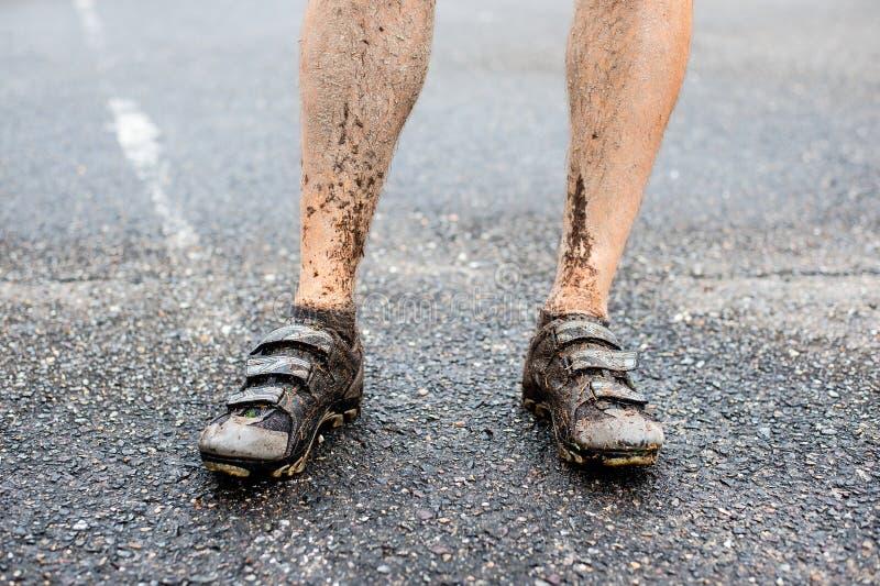 Λεπτομέρεια των ποδιών των ατόμων στην ανακύκλωση των ακίδων μετά από το γύρο στην υγρή και λασπώδη έκταση στοκ εικόνες με δικαίωμα ελεύθερης χρήσης