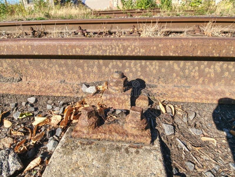Λεπτομέρεια των σκουριασμένων βιδών και του καρυδιού στον παλαιό σιδηρόδρομο Ξύλινος λαδωμένος δεσμός στοκ εικόνα με δικαίωμα ελεύθερης χρήσης
