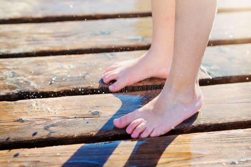 Λεπτομέρεια των υγρών ποδιών childs στην αποβάθρα, ηλιόλουστη θερινή ημέρα στοκ φωτογραφία