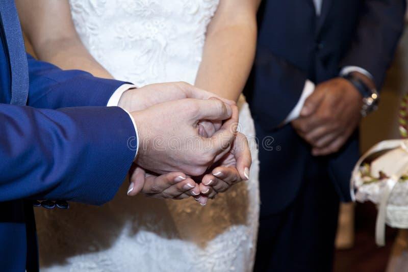 Λεπτομέρεια των χεριών της νύφης και του νεόνυμφου στοκ εικόνες