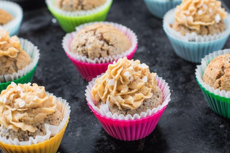 Λεπτομέρεια Muffins με το άλας καραμέλας και θάλασσας σε ένα μαύρο ψήσιμο στοκ εικόνα με δικαίωμα ελεύθερης χρήσης