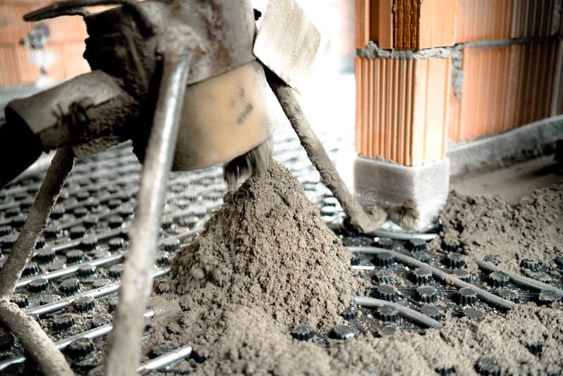Λεπτομέρειες εργοτάξιων οικοδομής - εργασία συγκεκριμένων αντλιών Ισοπέδωση κατεβατών πέρα από τη θέρμανση πατωμάτων στοκ φωτογραφία