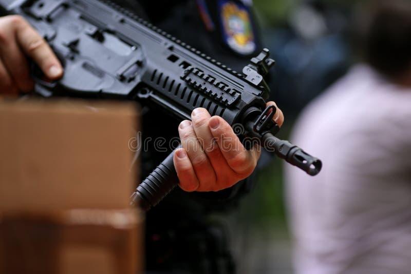 Λεπτομέρειες με τα χέρια ενός ατόμου που κρατά ένα αυτόματο τουφέκι στοκ εικόνα με δικαίωμα ελεύθερης χρήσης