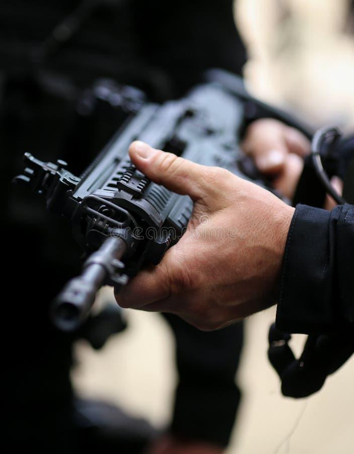 Λεπτομέρειες με τα χέρια ενός ατόμου που κρατά ένα αυτόματο τουφέκι στοκ εικόνες