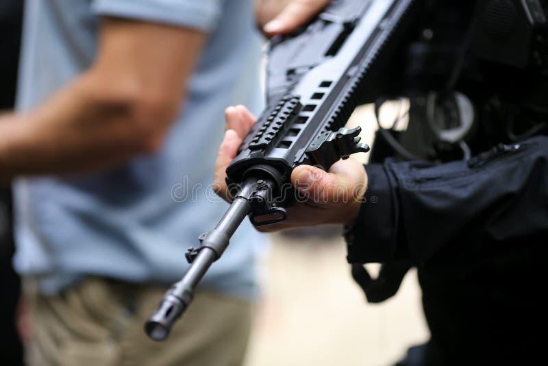 Λεπτομέρειες με τα χέρια ενός ατόμου που κρατά ένα αυτόματο τουφέκι στοκ φωτογραφίες με δικαίωμα ελεύθερης χρήσης