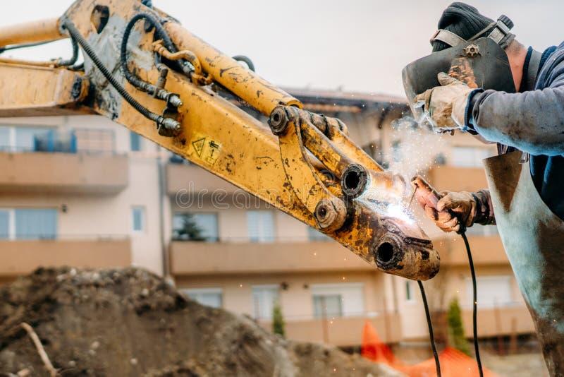 Λεπτομέρειες της συγκόλλησης εργαζομένων στο εργοτάξιο οικοδομής σπασμένος βραχίονας εκσκαφέων που καθορίζεται από το μηχανικό pr στοκ φωτογραφία με δικαίωμα ελεύθερης χρήσης