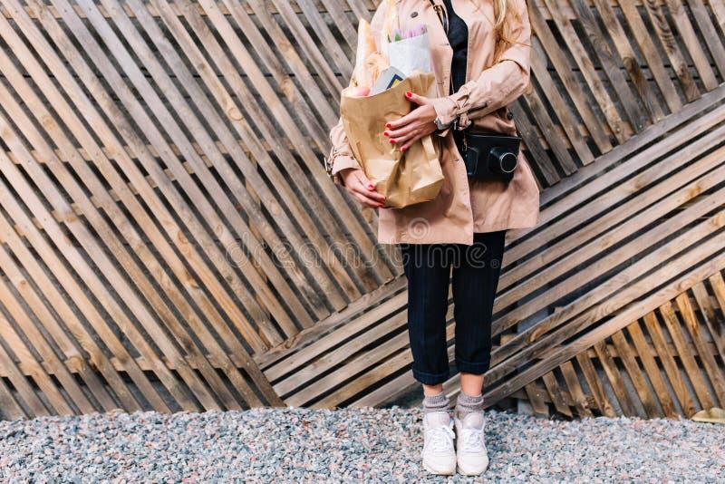Λεπτό κορίτσι στην κομψή περιστασιακή τοποθέτηση ενδυμασίας με την τσάντα αγορών στα χέρια στο ξύλινο υπόβαθρο Θηλυκό hipster στοκ εικόνα με δικαίωμα ελεύθερης χρήσης