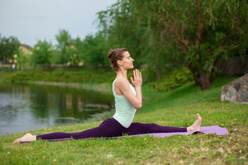 Λεπτό κορίτσι brunette που κάνει τη γιόγκα το καλοκαίρι σε έναν πράσινο χορτοτάπητα από τη λίμνη στοκ εικόνες