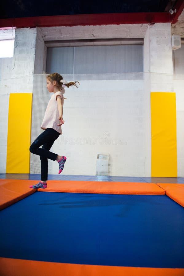 Λεπτό μικρό κορίτσι που πηδά στο εσωτερικό τραμπολίνο στοκ εικόνες