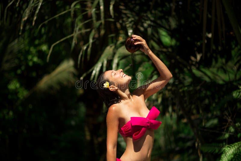 λεπτό νέο θηλυκό brunette που ποτίζεται με το φρέσκο γάλα καρύδων στο άγριο πράσινο υπόβαθρο ζουγκλών Βασιλικό τροπικό θέρετρο στοκ φωτογραφία με δικαίωμα ελεύθερης χρήσης
