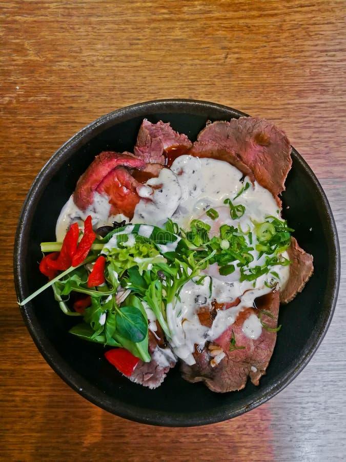Λεπτό τεμαχισμένο κάλυμμα Wagyu βόειου κρέατος ασφαλίστρου ιαπωνικό με την άσπρη ιταλική σάλτσα και σαλάτα σε ένα κύπελλο στοκ εικόνα