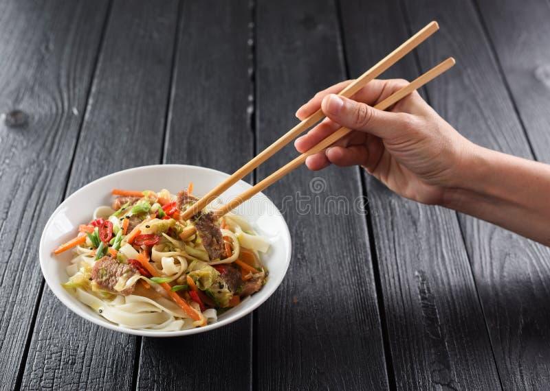 Λεπτό χέρι γυναικών με chopsticks που φθάνουν για το ασιατικό udon noodl στοκ εικόνες με δικαίωμα ελεύθερης χρήσης
