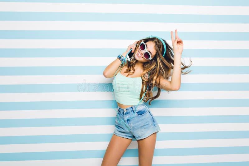 Λεπτό όμορφο κορίτσι που φορά τα καθιερώνοντα τη μόδα γυαλιά ηλίου που θέτουν πρόθυμα με το σημάδι ειρήνης που στέκεται στο ριγωτ στοκ φωτογραφία με δικαίωμα ελεύθερης χρήσης