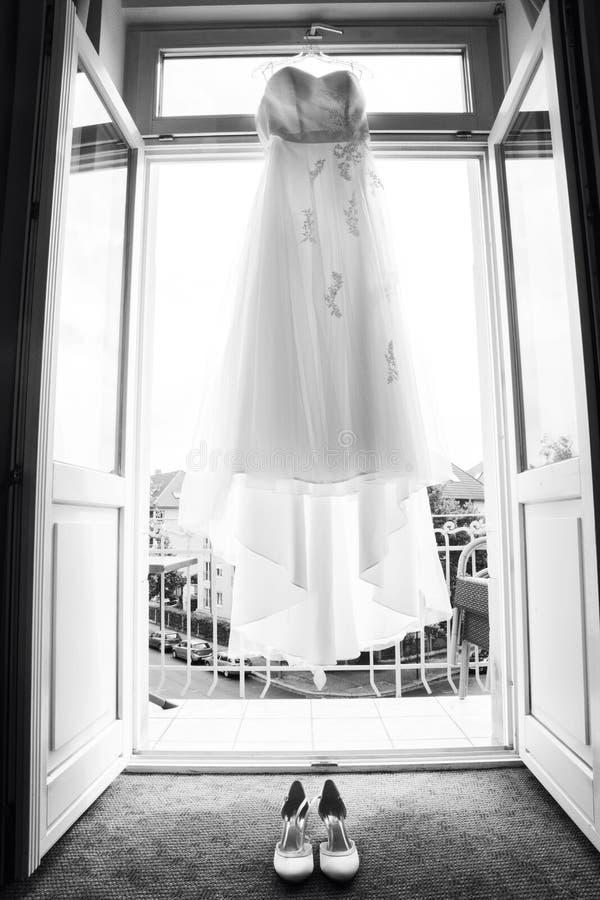 Λεπτό ύφασμα δαντελλών του άσπρων μακριών γαμήλιων φορέματος και των παπουτσιών στοκ φωτογραφία με δικαίωμα ελεύθερης χρήσης