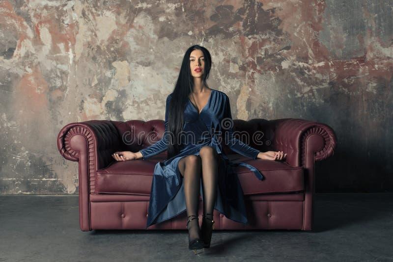 Λεπτό brunette σε ένα μπλε φόρεμα βελούδου στοκ φωτογραφίες