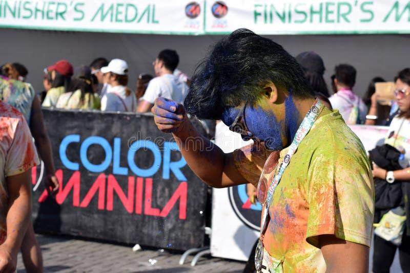 Λερωμένοι με τις χρωματισμένες χρωστικές ουσίες, οι νέοι που έχουν τη διασκέδαση στο χρώμα Μανίλα ακτινοβολούν τρέξιμο στοκ φωτογραφίες