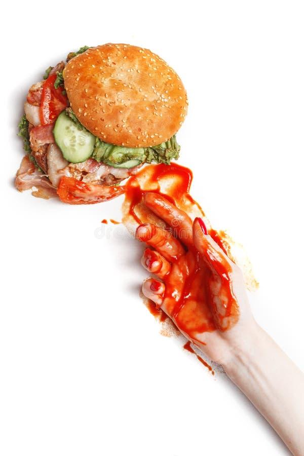 Λερωμένο στο κέτσαπ ένα χέρι κρατά burger Δημιουργική έννοια του γρήγορου φαγητού Άσπρη ανασκόπηση Κορυφή wiev διάστημα αντιγράφω στοκ εικόνες