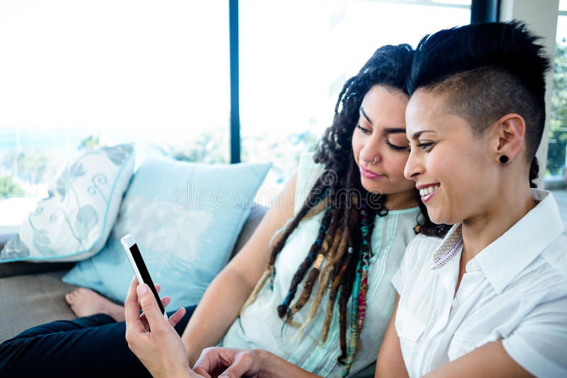 Λεσβιακό ζεύγος που εξετάζει το κινητό τηλέφωνο στοκ φωτογραφία