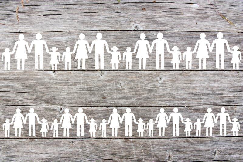 Λευκές οικογένειες εγγράφου στο ξύλινο υπόβαθρο στοκ φωτογραφίες
