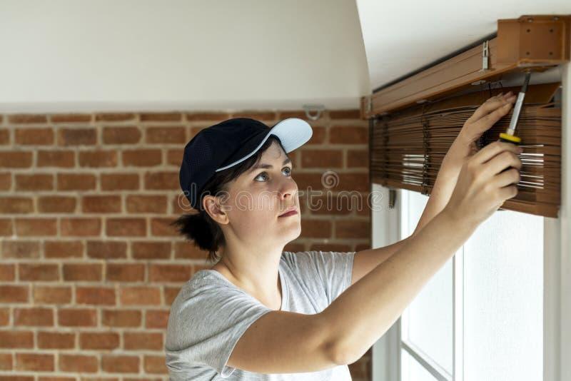 Λευκή γυναίκα που εγκαθιστά την κουρτίνα παραθύρων στοκ φωτογραφία