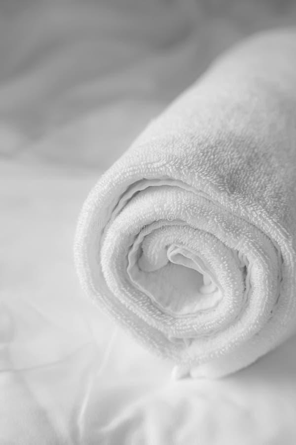 Λευκή πετσέτα σε λευκό φύλλο κρεβατιού στοκ φωτογραφία