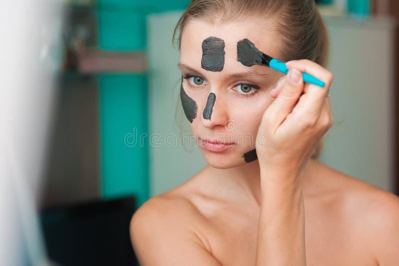 Λευκιά νέα γυναίκα που φορά μια μάσκα προσώπου στο σπίτι σε ένα τυρκουάζ υπόβαθρο Ευρωπαία γυναίκα στη μαύρη μάσκα για στενούς το στοκ εικόνα με δικαίωμα ελεύθερης χρήσης